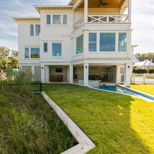 Diseño de fachada blanca, marinera, pequeña, de dos plantas, con revestimiento de aglomerado de cemento y tejado a cuatro aguas
