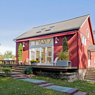Large farmhouse red three-story wood gable roof photo in Philadelphia