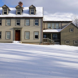 Large traditional beige three-story vinyl exterior home idea in New York