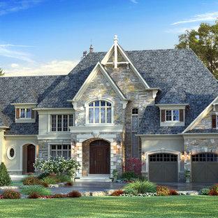 Modelo de fachada de casa gris, tradicional, grande, de dos plantas, con revestimientos combinados, tejado a la holandesa y tejado de teja de madera