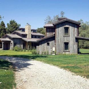 Exempel på ett stort rustikt grått hus, med två våningar, sadeltak och levande tak