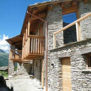 Foto de fachada gris, rústica, de tamaño medio, de dos plantas, con revestimiento de madera