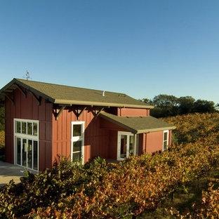 Foto della facciata di una casa piccola rossa classica con rivestimento in legno