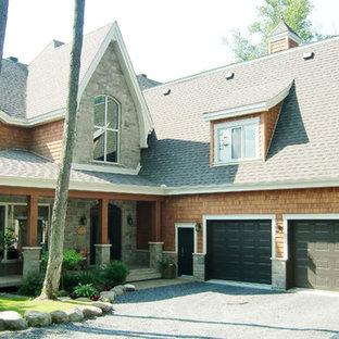 Ejemplo de fachada de casa naranja, rústica, de dos plantas, con revestimiento de madera y tejado de teja de madera