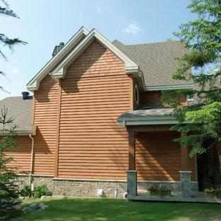 Foto de fachada de casa naranja, rústica, de dos plantas, con revestimiento de madera y tejado de teja de madera