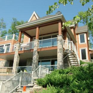 Diseño de fachada de casa naranja, rural, de dos plantas, con revestimiento de madera y tejado de teja de madera