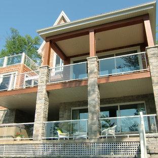 Imagen de fachada de casa naranja, rústica, de dos plantas, con revestimiento de madera y tejado de teja de madera