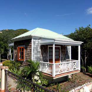 Example of a small island style one-story wood exterior home design in Other