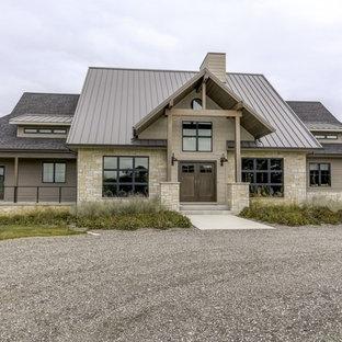 Esempio della facciata di una casa unifamiliare grande marrone country a due piani con rivestimenti misti, tetto a padiglione e copertura verde