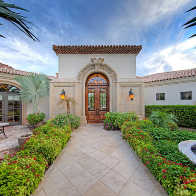 Example of a huge tuscan white one-story stucco exterior home design in Phoenix with a hip roof and a tile roof
