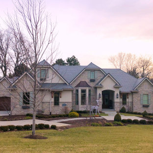 Mid-sized french country beige one-story stone house exterior photo in Omaha with a hip roof and a tile roof
