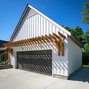 Immagine della facciata di una casa bianca country a due piani con rivestimento con lastre in cemento e tetto a capanna