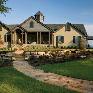 他の地域のトラディショナルスタイルのおしゃれな家の外観 (レンガサイディング、切妻屋根) の写真