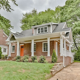 Example of a classic brown two-story brick gable roof design in Charlotte with a shingle roof