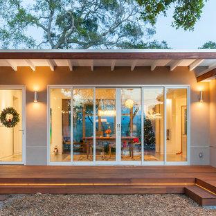Ejemplo de fachada beige, vintage, de tamaño medio, de una planta, con revestimiento de hormigón y tejado plano