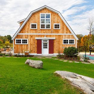 Ejemplo de fachada de casa beige, de estilo de casa de campo, de tamaño medio, de dos plantas, con revestimiento de madera, tejado a doble faldón y tejado de metal