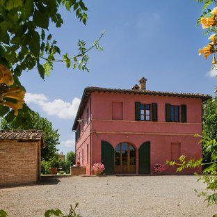 Design ideas for a mid-sized mediterranean two-storey stucco pink exterior in New York.