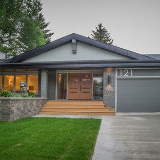 Ejemplo de fachada gris, ecléctica, de tamaño medio, a niveles, con revestimiento de ladrillo y tejado a dos aguas