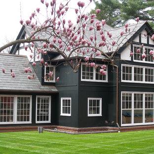 Modelo de fachada verde, de estilo de casa de campo, de tamaño medio, de dos plantas, con revestimiento de madera y tejado a dos aguas