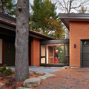 モントリオールのコンテンポラリースタイルのおしゃれな家の外観 (木材サイディング、茶色い外壁) の写真
