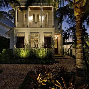 Foto della facciata di una casa unifamiliare bianca tropicale a due piani di medie dimensioni con tetto a capanna, rivestimento in legno e copertura in metallo o lamiera