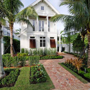 Inspiration for a mid-sized tropical two-storey white house exterior in Miami with a gable roof and a metal roof.