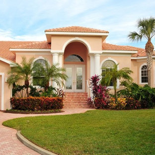Large elegant orange two-story stucco exterior home photo in Tampa with a tile roof
