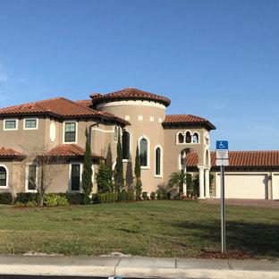 Ejemplo de fachada de casa gris, mediterránea, grande, de dos plantas, con tejado a cuatro aguas, revestimiento de estuco y tejado de teja de barro