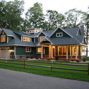 Imagen de fachada verde, campestre, grande, de dos plantas, con revestimiento de madera y tejado a cuatro aguas