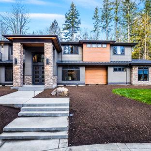 Ejemplo de fachada de casa verde, contemporánea, grande, de dos plantas, con revestimiento de vinilo, tejado a cuatro aguas y tejado de varios materiales