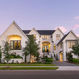 Ejemplo de fachada de casa blanca, clásica renovada, de tres plantas, con revestimiento de piedra, tejado a dos aguas y tejado de metal