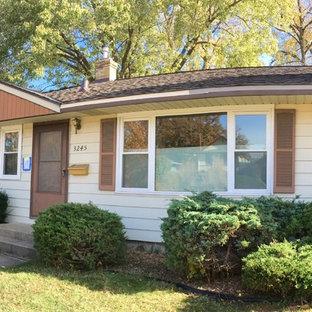 Diseño de fachada de casa beige, retro, de tamaño medio, de una planta, con revestimiento de vinilo y tejado de teja de madera
