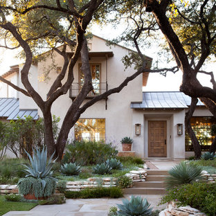 Inspiration for a mediterranean beige two-story gable roof remodel in Austin