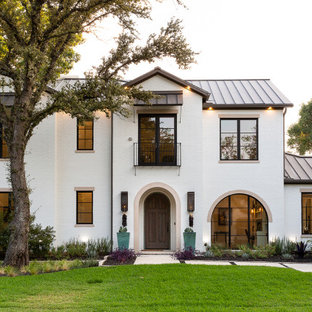 Design ideas for a mediterranean two-storey brick white house exterior in Dallas with a gable roof and a metal roof.