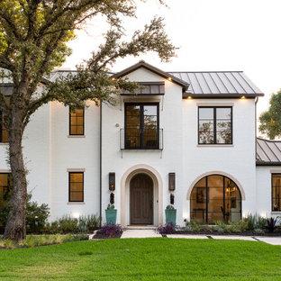 Неиссякаемый источник вдохновения для домашнего уюта: двухэтажный, кирпичный, белый частный загородный дом в средиземноморском стиле с двускатной крышей, металлической крышей и серой крышей