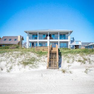 Свежая идея для дизайна: двухэтажный, серый частный загородный дом в морском стиле с вальмовой крышей, металлической крышей и серой крышей - отличное фото интерьера