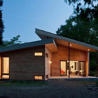 Esempio della facciata di una casa unifamiliare piccola marrone contemporanea a un piano con rivestimento in legno, tetto a una falda e copertura in metallo o lamiera