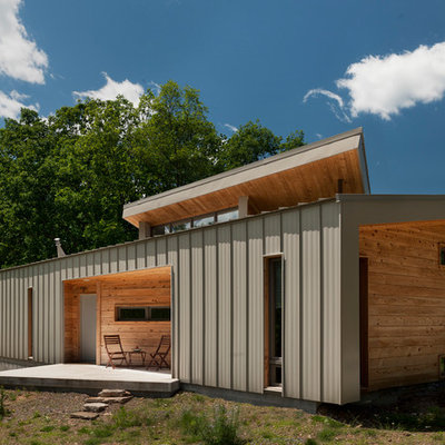 Example of a small trendy brown one-story wood house exterior design in DC Metro with a shed roof and a metal roof