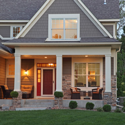 Example of a mid-sized classic gray two-story stone gable roof design in Minneapolis