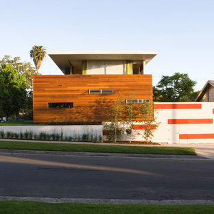 Imagen de fachada roja, retro, de dos plantas, con revestimiento de madera y tejado plano