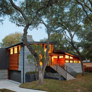 Imagen de fachada de casa multicolor, retro, a niveles, con revestimientos combinados y tejado de un solo tendido