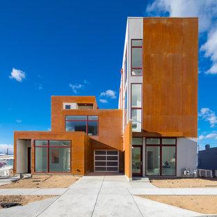 Ejemplo de fachada de casa bifamiliar naranja, contemporánea, grande, de tres plantas, con revestimiento de metal y tejado plano