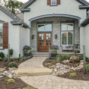Example of a large transitional gray two-story stucco exterior home design in Kansas City