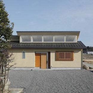 Ejemplo de fachada de casa beige, de estilo zen, pequeña, de una planta, con revestimiento de estuco, tejado de un solo tendido y tejado de metal