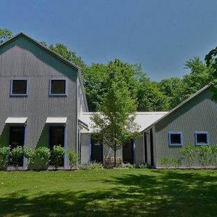 Foto de fachada de casa gris, industrial, extra grande, de dos plantas, con revestimiento de metal, tejado a dos aguas y tejado de metal