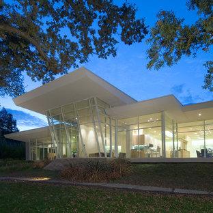 Modelo de fachada blanca, minimalista, grande, de una planta, con revestimiento de vidrio y tejado plano