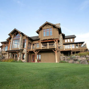 Large mountain style brown two-story mixed siding exterior home photo in Other with a shingle roof