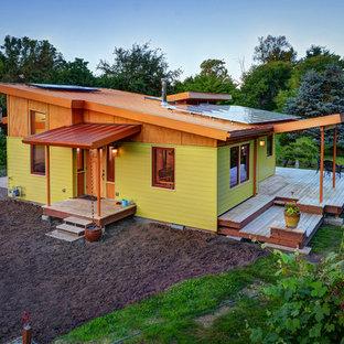 Foto de fachada amarilla, actual, de una planta, con tejado de un solo tendido