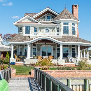 Modelo de fachada verde, clásica, grande, de tres plantas, con revestimiento de madera y tejado a dos aguas
