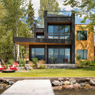 Huge trendy black three-story wood flat roof photo in Other